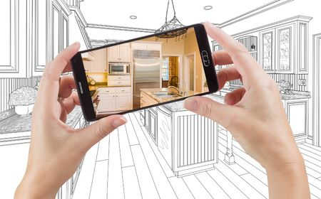 holding smart phone: Hands Holding Smart Phone Displaying Photo of Custom Kitchen Drawing Behind.