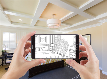 Hands Holding Smart Phone Displaying Drawing of Custom Bedroom Photo Behind.
