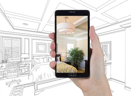 holding smart phone: Hand Holding Smart Phone Displaying Photo of Custom Bedroom Drawing Behind. Stock Photo