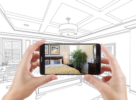 holding smart phone: Hands Holding Smart Phone Displaying Photo of Custom Bedroom Drawing Behind.