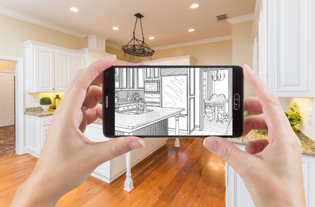 Hands Holding Smart Phone Displaying Drawing of Custom Kitchen Photo Behind.