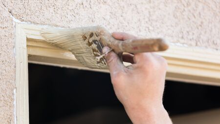 finishing touches: Professional Painter Cutting In With A Brush to Paint House Door Frame.