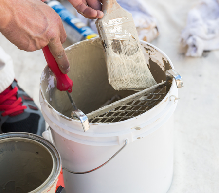 finishing: Professional Painter Loading Paint Onto His Brush From A Bucket. Stock Photo