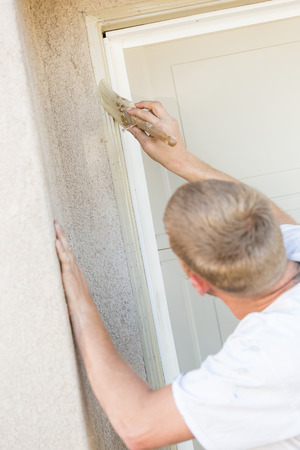 finishing touches: Professional Painter Cutting In With A Brush to Paint Garage Door Frame. Stock Photo
