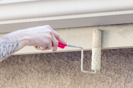 curb appeal: Professional Painter Using A Small Roller to Paint House Fascia.