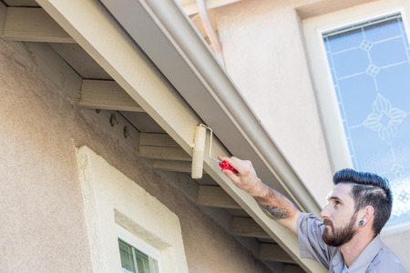 finishing touches: Professional Painter Using A Small Roller to Paint House Fascia.