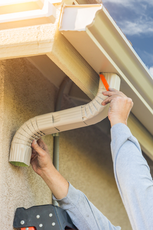 Worker Attaching Aluminum Rain Gutter and Down Spout to Fascia of House. Banque d'images