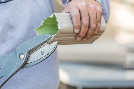 Trabajador que corta el canalón de aluminio de la lluvia con tijeras pesadas Foto de archivo - 72273429