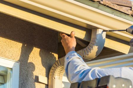 Worker Attaching Aluminum Rain Gutter and Down Spout to Fascia of House. Foto de archivo