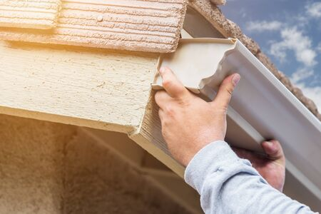 attaching: Worker Attaching Aluminum Rain Gutter to Fascia of House.