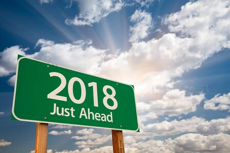 next year: 2018 Green Road Sign Over Dramatic Clouds and Sky. Stock Photo