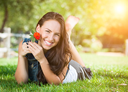 Attractive Mixed Race Girl Daydreaming Laying in Grass Outdoors with Flower.