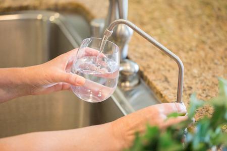 新鮮な逆浸透膜を注いで、女は、キッチンでガラスに水を精製しました。