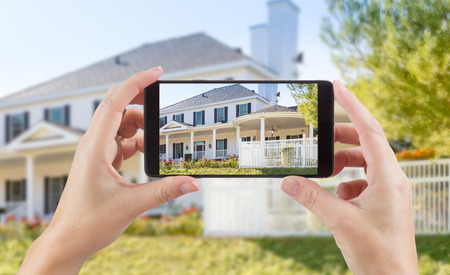Female Hands Holding Smart Phone Displaying Photo of House Behind.