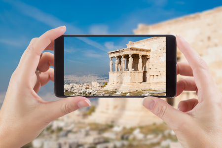 caryatids: Female Hands Holding Smart Phone Displaying Photo of Caryatids in Erechtheum from Athenian Acropolis, Greece Behind.