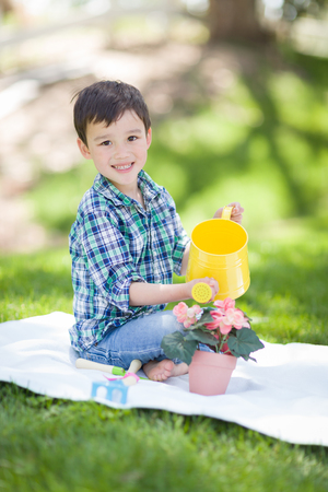 Mixed Race Young Boy Watering His Potted Flowers Outside On The Grass Stock Photo