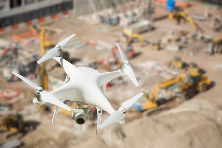 site: Unmanned Aircraft System (UAV) Quadcopter Drone In The Air Over Construction Site.
