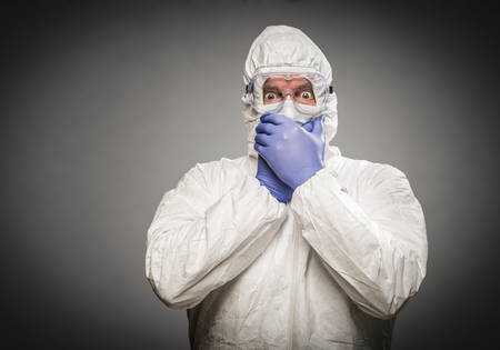 Man Covering Mouth With Hands Wearing HAZMAT Protective Clothing Against A Gray Background.