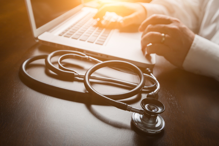 researching: Medical Stethoscope Resting on Desk As Male Hands Type on Computer Keyboard. Stock Photo