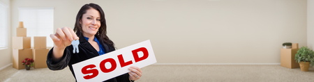 Banner of Hispanic Woman Inside Room with Boxes Holding House Keys and Sold For Sale Real Estate Sign. photo