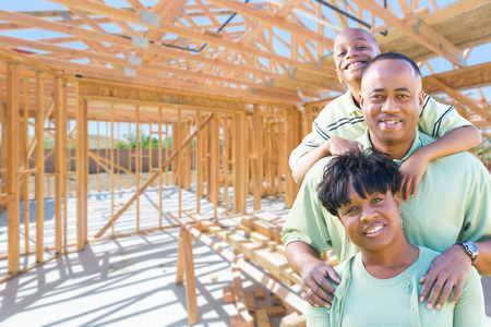 Young African American Family On Site Inside Their New Home Construction Framing. photo