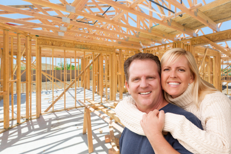 Happy Excited Couple On Site Inside Their New Home Construction Framing. photo