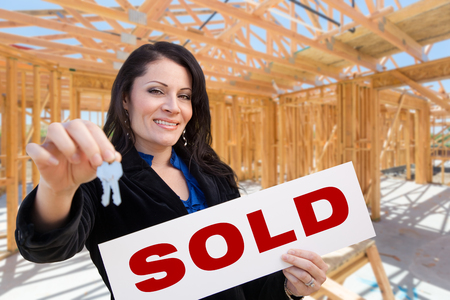 Hispanic Woman With Keys and Sold Sign On Site Inside New Home Construction Framing. photo