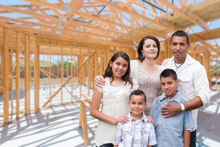 Young Hispanic Family On Site Inside New Home Construction Framing. Stockfoto