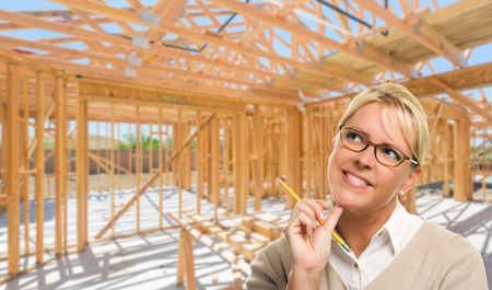 Pensive Woman with Pencil On Site Inside New Home Construction Framing. photo