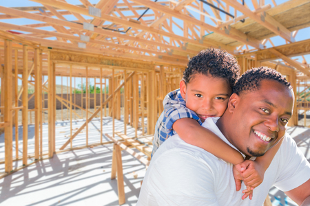 Young African American Father and Mixed Race Son On Site Inside Their New Home Construction Framing.