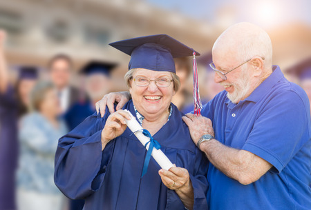 70s: Senior Adult Woman In Cap and Gown Being Congratulated By Husband At Outdoor Graduation Ceremony.