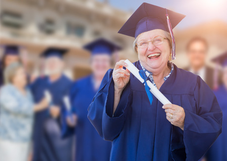 senior adult woman: Happy Senior Adult Woman In Cap and Gown At Outdoor Graduation Ceremony. Stock Photo