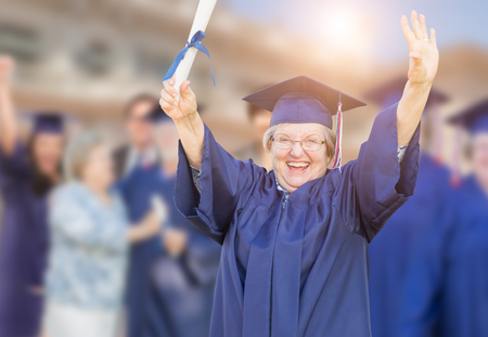 Happy Senior Adult Woman In Cap and Gown At Outdoor Graduation Ceremony. photo