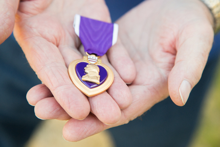 Senior Man Holding The Military Purple Heart Medal In His Hands. Foto de archivo