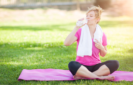 young adult woman: Young Fit Adult Woman Outdoors On Her Yoga Mat with Towel Drinking From Her Water Bottle. Stock Photo