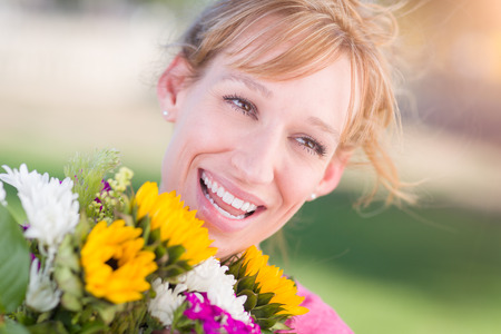 Outdoor Portrait of an Excited Young Adult Brown Eyed Woman Holding a Bouquet of Flowers.