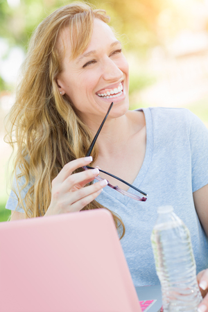 Young Adult Woman With Glasses Outdoors Using Her Laptop. Stock Photo