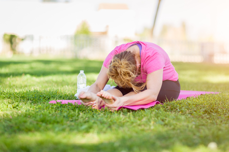 young adult woman: Young Fit Flexible Adult Woman Outdoors on The Grass With Yoga Mat Stretching Her Legs.