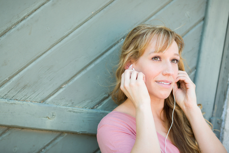 young adult woman: Outdoor Portrait of Young Adult Brown Eyed Woman Listening To Music with Earphones.