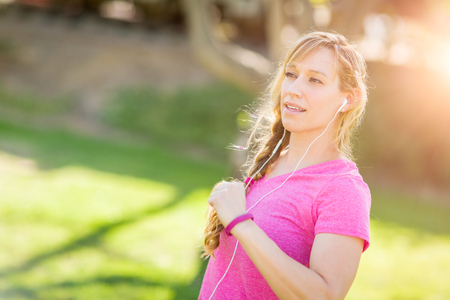 young adult woman: Young Fit Adult Woman Outdoors During Workout Listening To Music with Earphones. Stock Photo