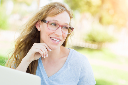 young adult woman: Young Adult Woman Wearing Glasses Outdoors Using Her Laptop.