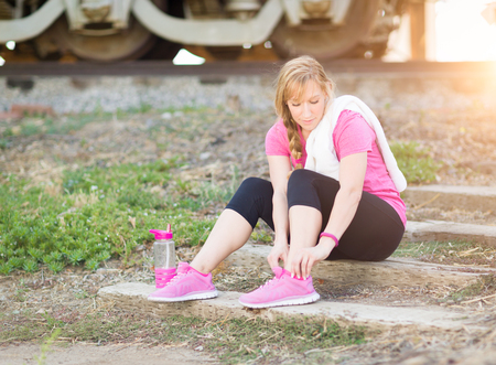 young adult woman: Young Adult Woman Outdoors With Towel and Water Bottle Tying Her Shoe Ready for Workout.