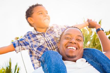 Mixed Race Son and African American Father Playing Piggyback Outdoors Together. Stock Photo
