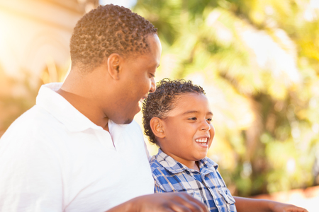 Mixed Race Son and African American Father Playing Outdoors Together. photo