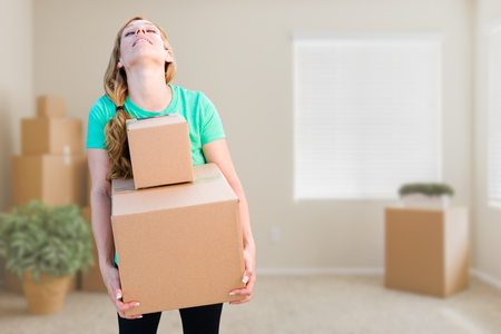 Tired Young Adult Woman Holding Moving Boxes In Empty Room In A New House.