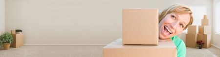 young adult woman: Banner of Happy Young Adult Woman Holding Moving Boxes In Empty Room In A New House.
