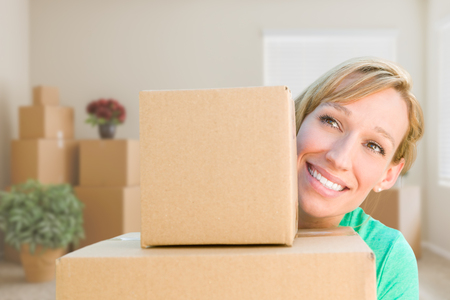 thrilled: Happy Young Adult Woman Holding Moving Boxes In Empty Room In A New House.