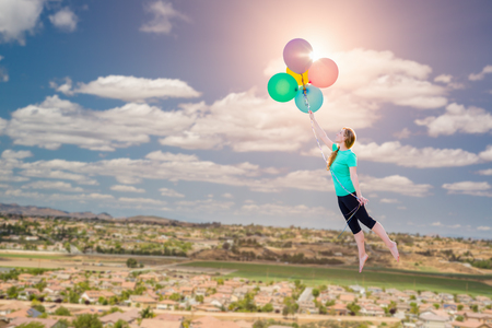 liberate: Young Girl Being Carried Up and Away By Balloons That She Is Holding Above The Town Below.