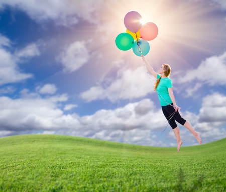 Young Girl Being Carried Up and Away By Balloons That She Is Holding Above The Grass Field Below.