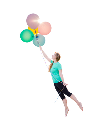Young Girl Being Carried Up and Away By Balloons That She Is Holding Isolated On A White Background. Banco de Imagens